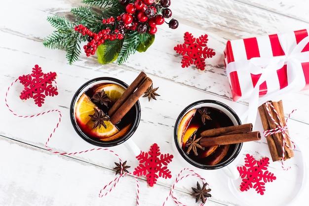 Горячий глинтвейн в кружке на белом деревянном фоне. традиционный согревающий зимний винный напиток с ароматными специями. вид сверху.
