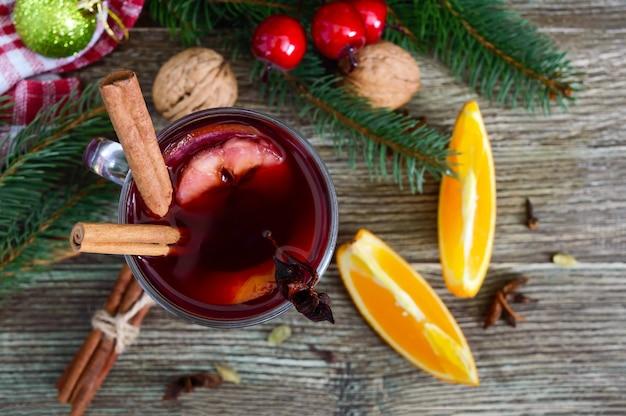 나무 테이블에 유리 머그잔에 뜨거운 mulled 와인. 와인, 주스, 향신료, 조미료, 과일을 기본으로 한 향기로운 전통 겨울 음료. 확대. 상위 뷰