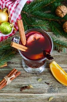 나무 테이블에 유리 머그잔에 뜨거운 mulled 와인. 와인, 주스, 향신료, 조미료, 과일을 기본으로 한 향기로운 전통 겨울 음료. 확대
