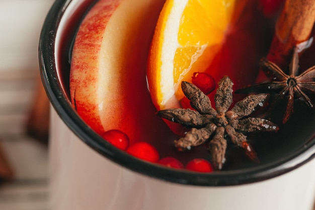 Hot mulled wine in rustic cup close up
