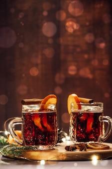 Горячий глинтвейн с фруктами и специями на деревянном столе. зимний согревающий праздничный напиток.