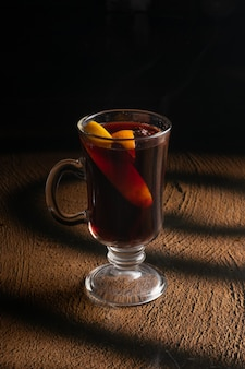 Hot mulled wine with orange slices and star anise in a clear glass glass with a handle.