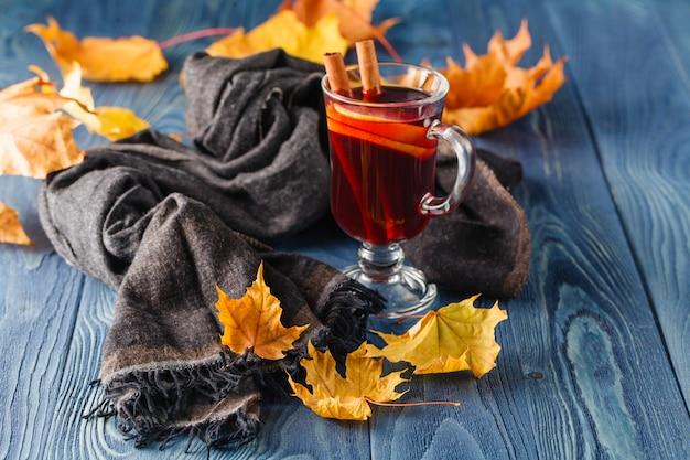 Горячий глинтвейн со специями (корица, анис) и лимоном на вязаном шарфе. опавшие листья. осенняя тема.