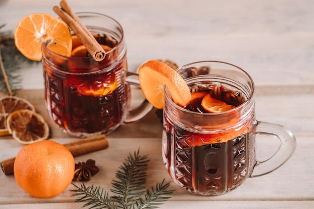 木製の背景にガラスのカップにスパイスとホットホットワイン。クリスマスの温かい飲み物。