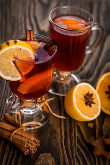 Hot mulled wine with spicy spices and orange. lemon, cinnamon and cardamom on a wooden bac