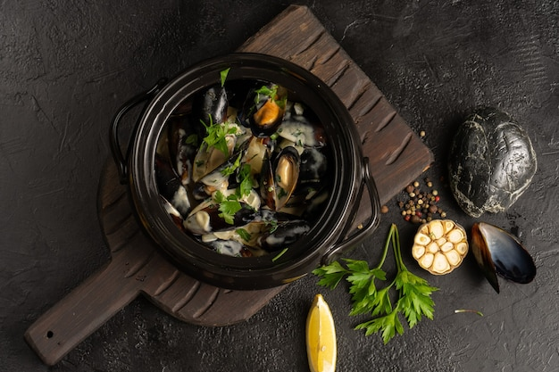 Hot mussels with sauce, parsley, lemon and garlic in a black pot. a hot asian seafood dish in a deep bowl on a black table. top view.