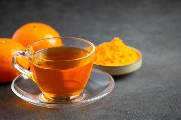 テーブルの上のホットオレンジティーとフレッシュオレンジ