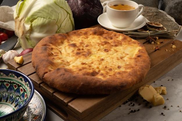 Горячий осетинский пирог с капустой, зеленью и сыром рядом с декоративной национальной узбекской керамической посудой с традиционным узором.
