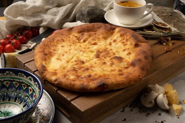 Горячий осетинский пирог с сыром и грибами рядом с декоративными национальными узбекскими керамическими блюдами с традиционным узором.