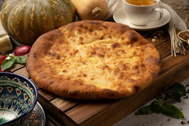 Горячий осетинский пирог с тыквенной начинкой и зеленью рядом с декоративной национальной узбекской керамической посудой с традиционным узором.