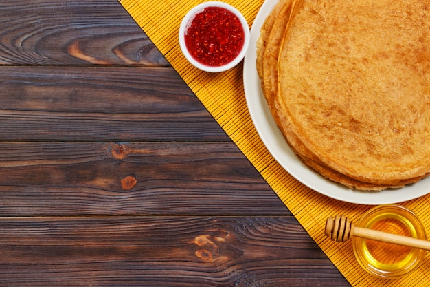 Hot pancakes with sprinkled maple syrup and raspberry jam.