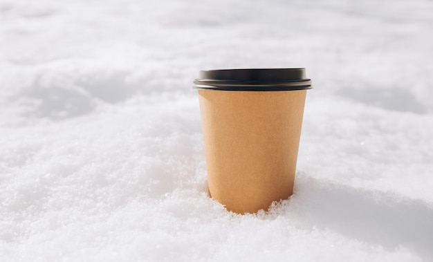 Hot paper craft cup of coffee on the snow on a morning. take away or delivery concept. copy space. winter lifestyle. place for your text or logo on mug, mockup