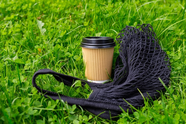 朝の草の上に黒いバッグとコーヒーのホットペーパークラフトカップ。テイクアウトまたは配達の概念。スペースをコピーします。夏のライフスタイル。マグカップ、モックアップにテキストやロゴを配置します