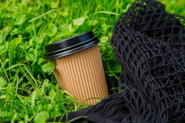 뜨거운 종이 공예품 아침에 잔디에 검은 가방이 달린 커피 한 잔. 테이크 아웃 또는 배달 개념. 공간을 복사합니다. 여름 라이프 스타일입니다. 머그, 목업에 텍스트 또는 로고 배치