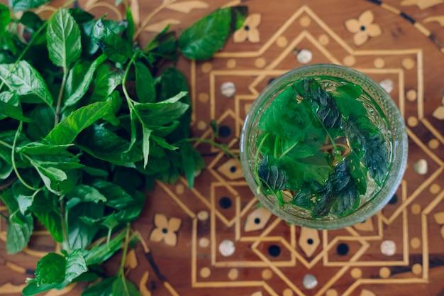 Горячий травяной арабский чай с мятой и свежие листья мяты