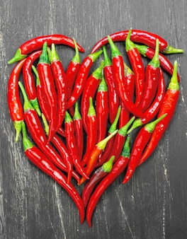 Hot peppers forming a heart on old wooden table black