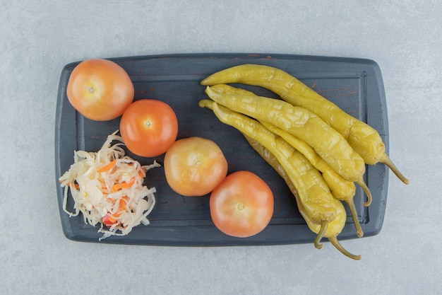 Острый перец, помидоры и квашеная капуста на доске на мраморной поверхности