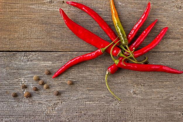 Hot peppers with spices on wooden background