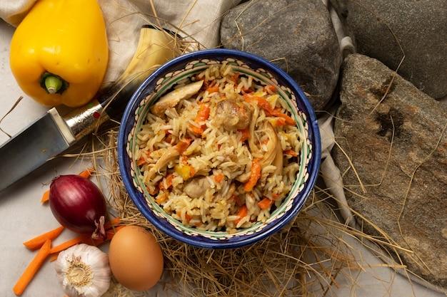 伝統的なパターンの装飾的なウズベキスタンの国民のボウルに鶏の切り身が入った熱いピラフ。ご飯、肉、野菜にスパイシーなスパイスを加えた定番のオリエンタル料理