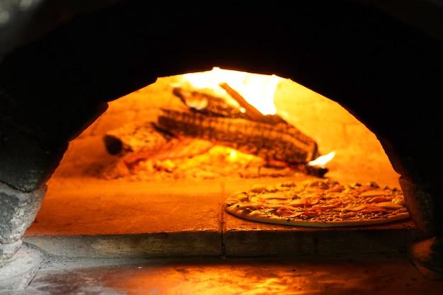 진짜 이탈리아 석기 난로에서 뜨거운 피자