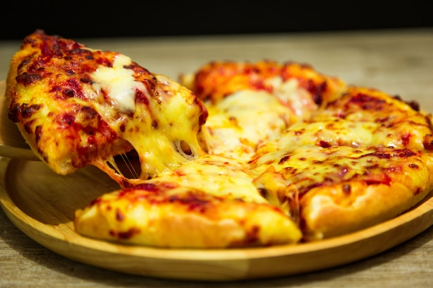 Hot pizza slice with dripping mozzarella cheese.
