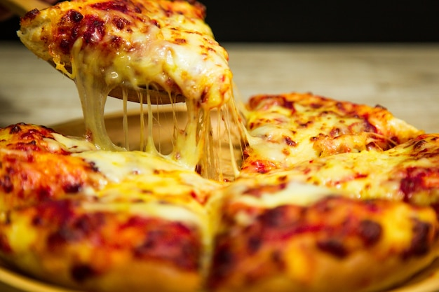 Hot pizza slice with melting cheese.