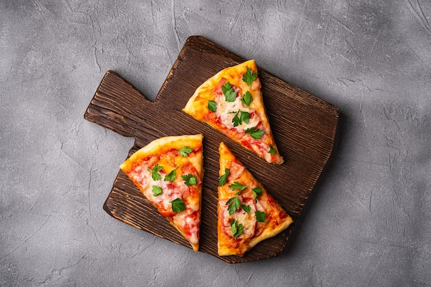 Hot pizza slices with mozzarella cheese, ham, tomato and parsley on brown wooden cutting board, stone concrete surface, top view