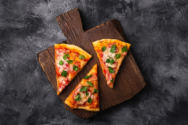 Hot pizza slices with mozzarella cheese, ham, tomato and parsley on brown wooden cutting board, stone concrete table, top view