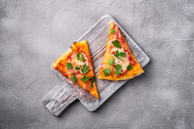 Hot pizza slices with mozzarella cheese, ham, tomato and parsley on wooden cutting board, stone concrete table, top view