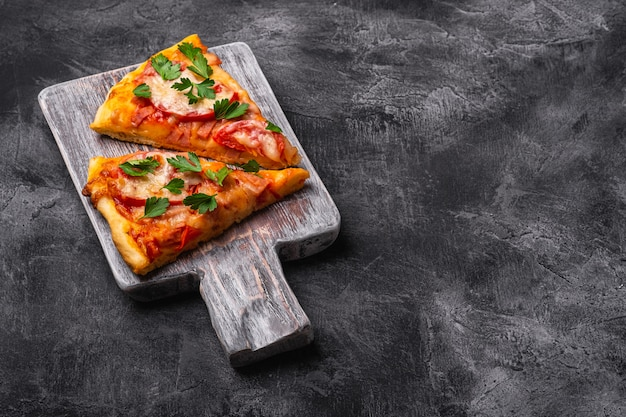 Hot pizza slices with mozzarella cheese, ham, tomato and parsley on wooden cutting board
