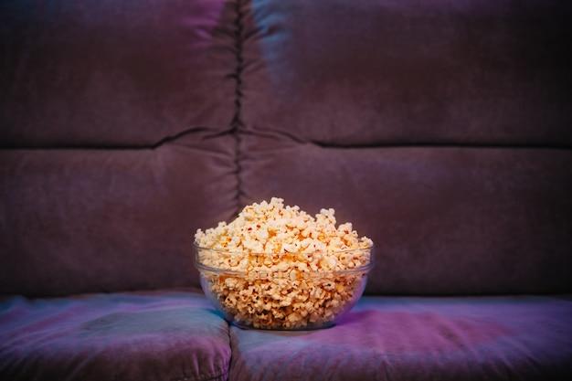 Горячий попкорн в миске на диване в ожидании просмотра телевизора