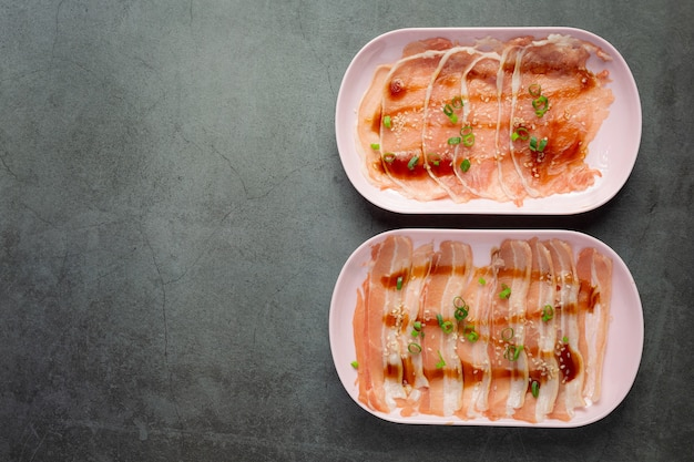 Сябу в горячем горшочке; сырая свежая нарезанная свинина в тарелке