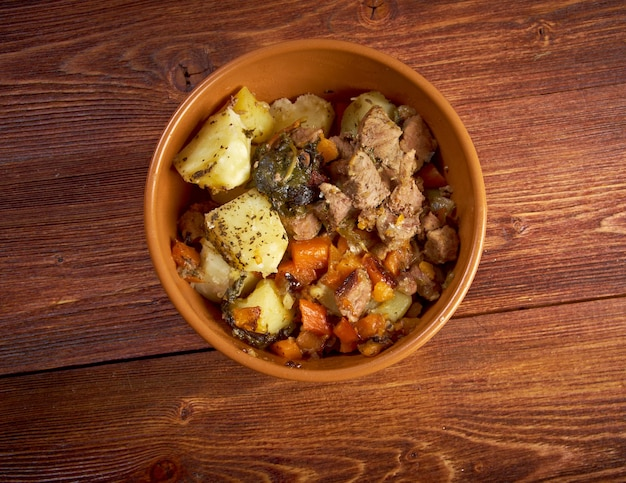 Тушеное мясо в горячем горшочке с морковью и картофелем. деревенская кухня. фермерский стиль.