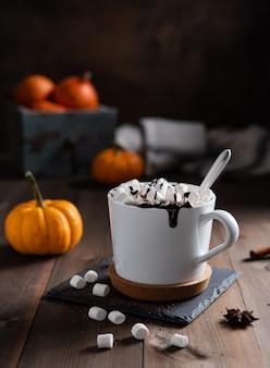 木製のテーブルの上の白いマグカップにマシュマロとチョコレートが入ったホットパンプキンラテ。正面図。暗い写真