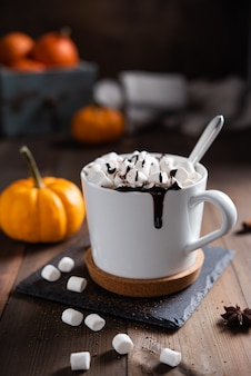 木製のテーブルの上の白いマグカップにマシュマロとチョコレートが入ったホットパンプキンラテ。マクロとクローズアップビュー。暗い写真