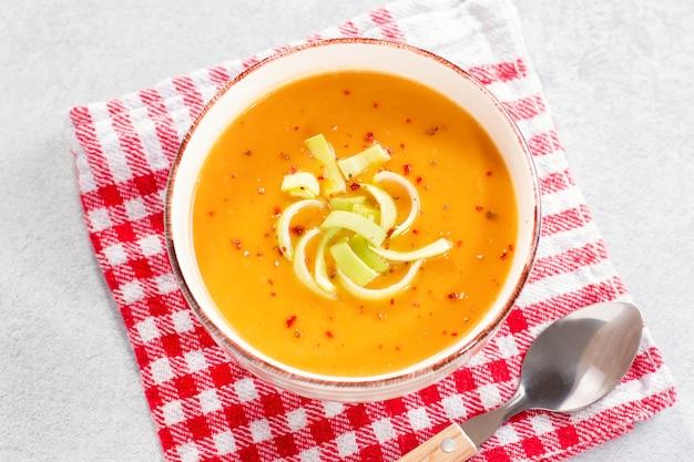 コンクリートの背景にスパイスとホットカボチャまたはニンジンクリームのスープ。秋のスパイシーなスープ、健康的な食事、上面図のクローズアップ