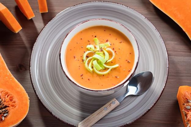 木製の背景にスパイスとホットカボチャまたはニンジンクリームスープ。秋のスパイシーなスープ、健康的な食事、上面図のクローズアップ