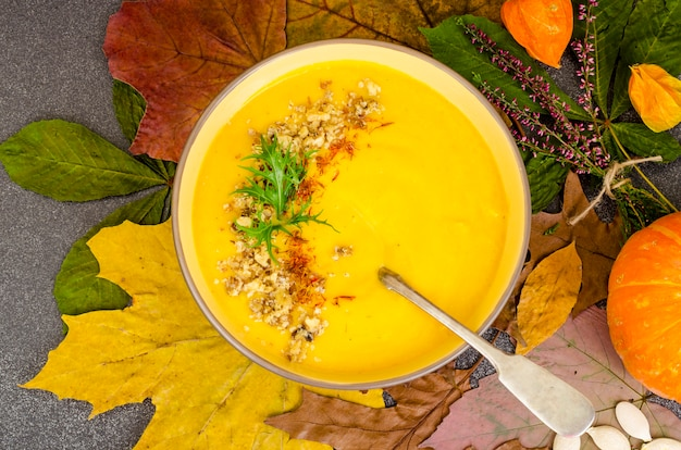 Hot pumpkin soup on background of dried autumn leaves.