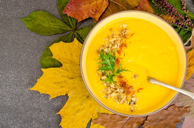 Hot pumpkin soup on dried autumn leaves.