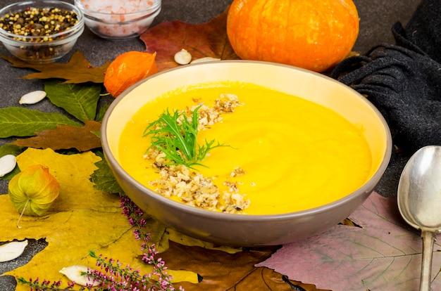 乾燥した秋の葉の背景に熱いカボチャのスープ。