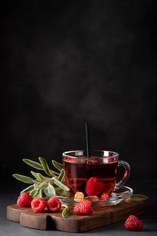 Горячий малиновый чай с шалфеем и медом в стеклянной кружке крупным планом