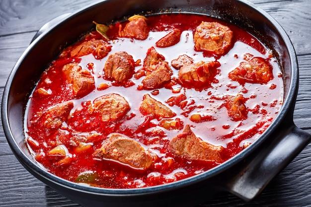 Горячий красный чили и тушеная свинина или карне адобада в голландской духовке на черном деревянном столе, мексиканская кухня, горизонтальный вид сверху, крупный план