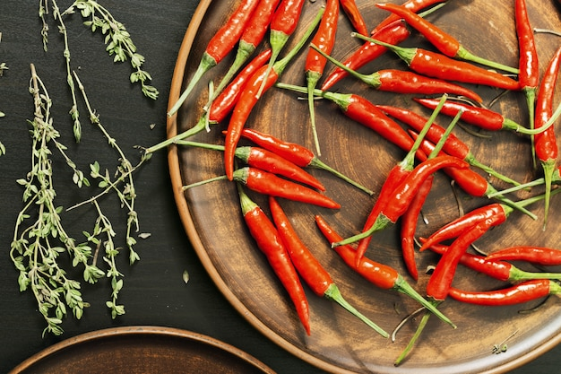 Hot red chili peppers and lemon thyme on clay brown homemade flat plate. top view and low-key lighting.