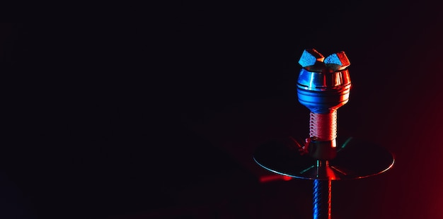 Hot red coals for hookah shisha in a ceramic metal bowl with red blue neon lighting on a black background with a copy space