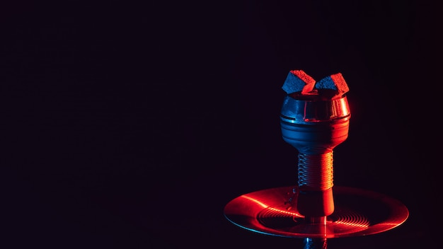 Hot red coals for hookah shisha in a ceramic metal bowl with red blue neon lighting