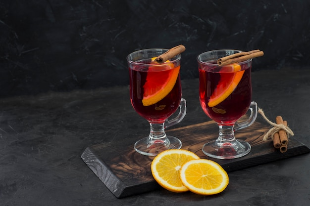 Hot red drink in transparent circles with cinnamon and orange