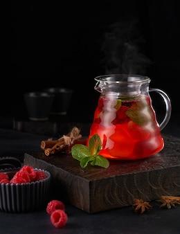 Горячий красный фруктовый чай с малиной в стеклянном чайнике с мятой на деревянном фоне