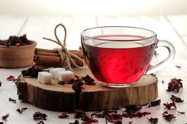 白い木製のテーブルの上にカップで熱い赤いカルカデ茶