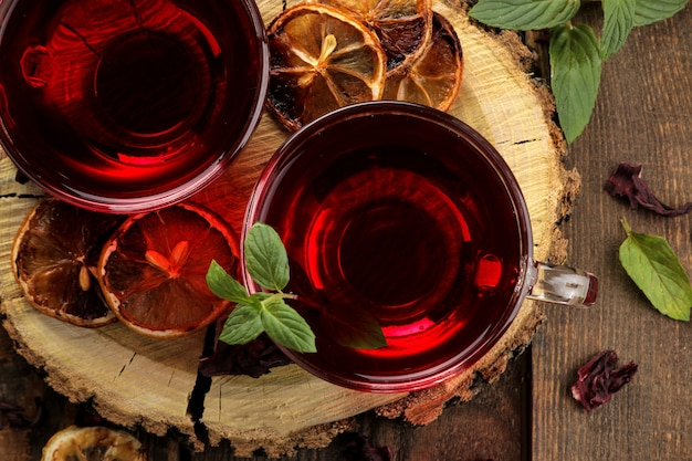 꿀과 민트를 곁들인 뜨거운 레드 카케이드 차. 가을 또는 겨울 청량 음료. 갈색 나무 테이블에. 위에서 보기