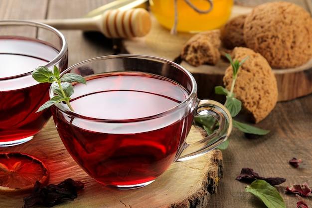 꿀과 민트를 곁들인 뜨거운 레드 카케이드 차. 가을 또는 겨울 청량 음료. 갈색 나무 테이블에.